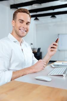 Glücklicher junger geschäftsmann, der smartphone im büro arbeitet und benutzt