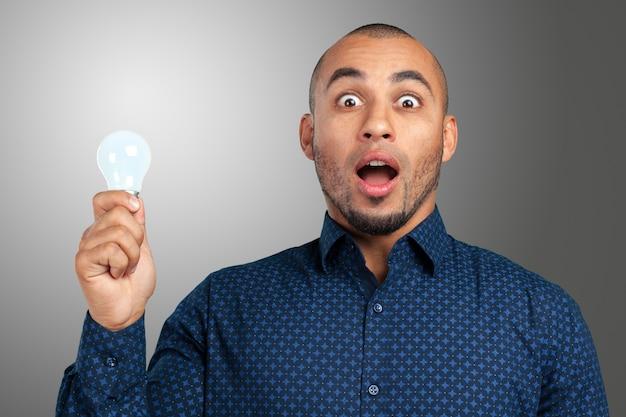 Glücklicher junger geschäftsmann holding light bulb