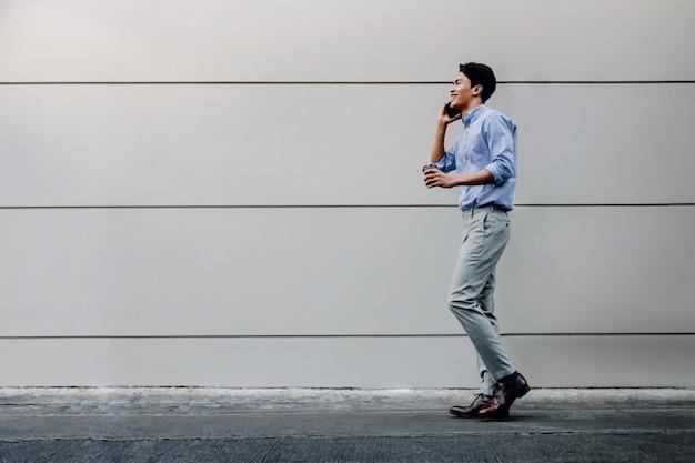 Glücklicher junger geschäftsmann in der freizeitkleidung unter verwendung des mobiltelefons beim gehen durch die städtische gebäudewand. lebensstil der modernen menschen.