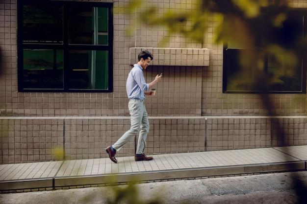 Glücklicher junger geschäftsmann in freizeitkleidung verwenden oder lesen des mobiltelefons beim gehen durch das städtische gebäude. lebensstil der modernen menschen. seitenansicht. in voller länge