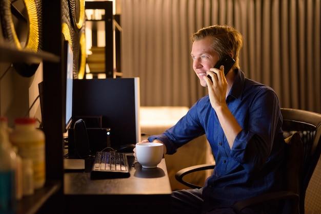 Glücklicher junger geschäftsmann mit kaffee, der am telefon spricht, während er spät abends von zu hause aus arbeitet