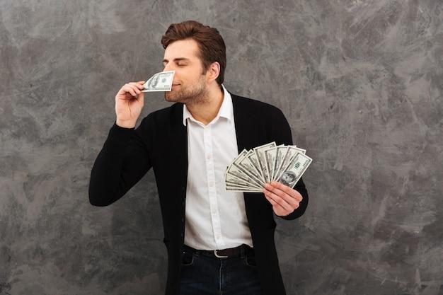 Glücklicher junger geschäftsmann riechen geld.