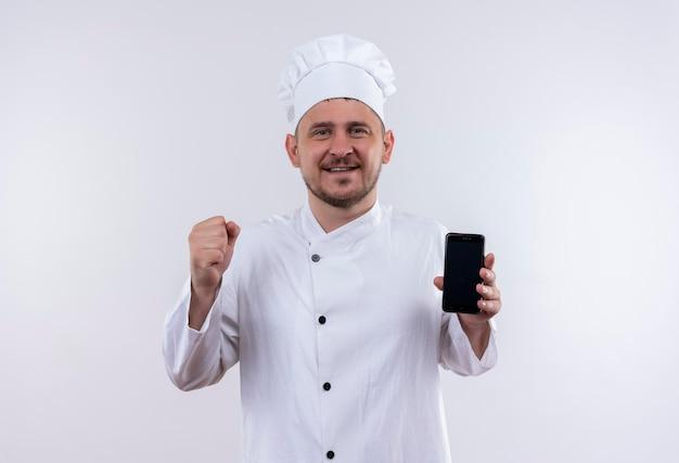 Glücklicher junger gutaussehender koch in kochuniform, der handy hält und die faust isoliert auf weißer wand hebt