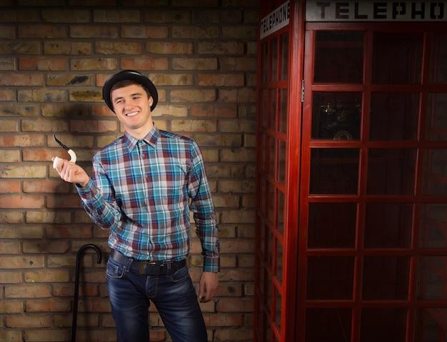 Glücklicher junger gutaussehender mann in kariertem hemd und jeans mit trendigem hut, der pfeife in der nähe der telefonzelle auf einem backsteinmauer-hintergrund hält.