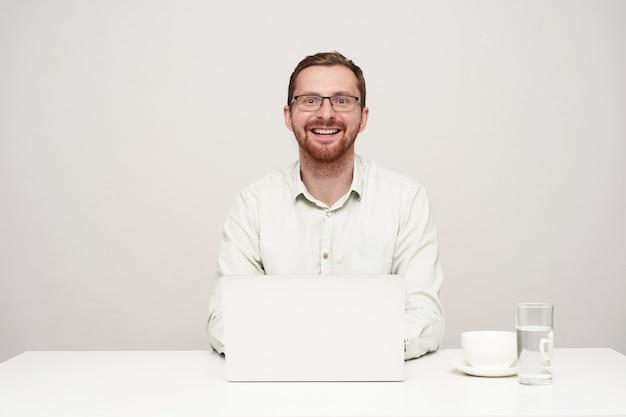 Glücklicher junger gutaussehender unrasierter mann in der brille, der gern mit breitem lächeln in die kamera schaut, während er mit seinem laptop über weißem hintergrund arbeitet und in hochstimmung ist