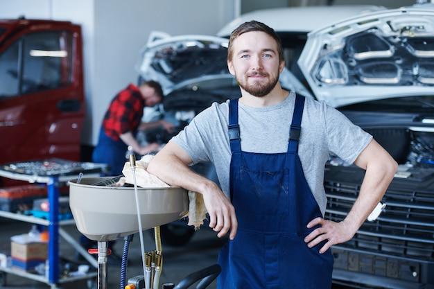 Glücklicher junger handwerker im blauen overall, der sie in der werkstatt ansieht