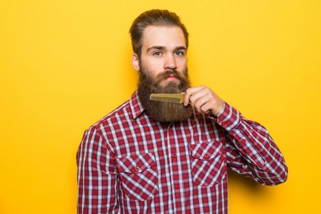 Glücklicher junger hipster-mann kämmt seinen bart und schnurrbart auf gelbem raum.