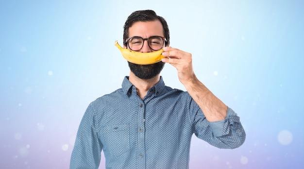 Glücklicher junger hipstermann mit banane