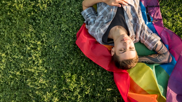 Glücklicher junger homosexueller, der auf lichtung liegt