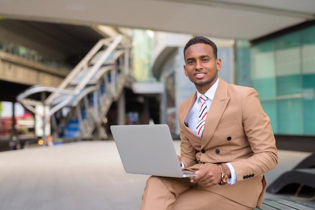 Glücklicher junger hübscher afrikanischer geschäftsmann, der laptop beim sitzen in der stadt im freien verwendet