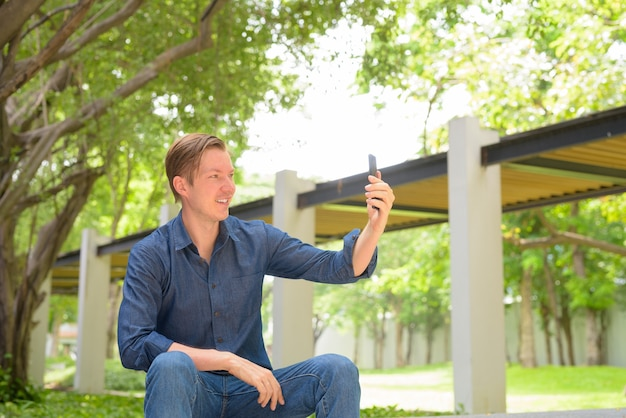 Glücklicher junger hübscher blonder geschäftsmann, der selfie nimmt und am park sitzt
