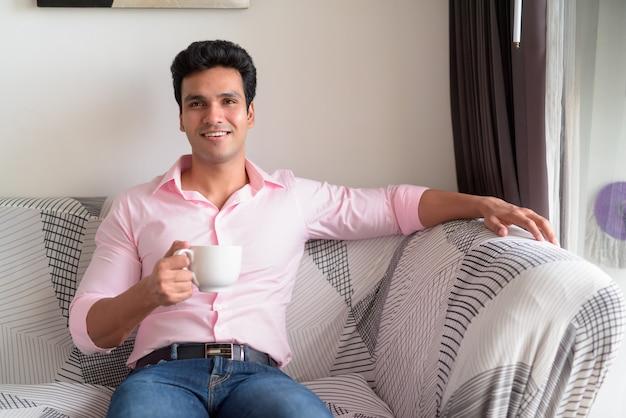 Glücklicher junger hübscher indischer geschäftsmann, der kaffee im wohnzimmer zu hause trinkt