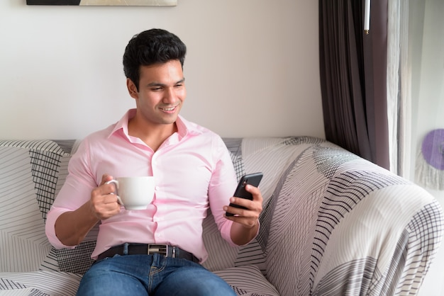 Glücklicher junger hübscher indischer geschäftsmann, der kaffee trinkt, während telefon zu hause verwendet wird