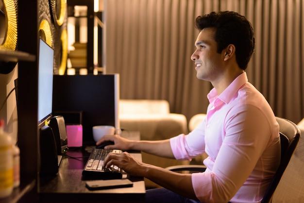 Glücklicher junger hübscher indischer geschäftsmann, der spät in der nacht zu hause überstunden macht