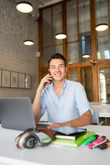 Glücklicher junger hübscher mann, der im mitarbeitenden büro sitzt