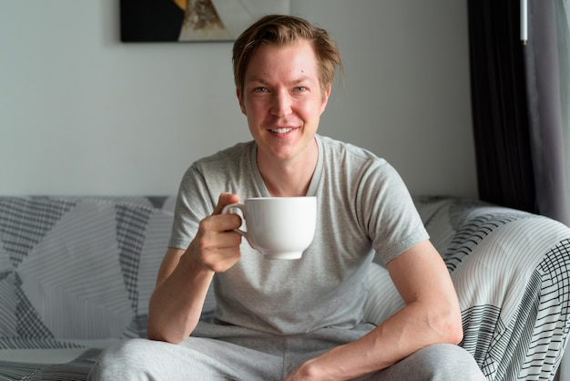 Glücklicher junger hübscher mann, der kaffee im wohnzimmer zu hause trinkt