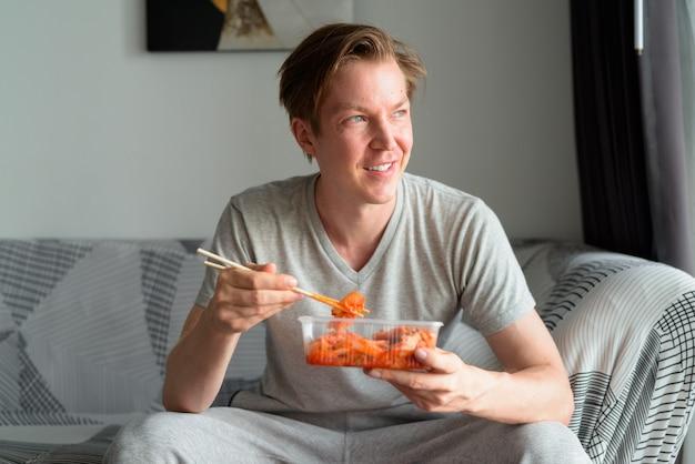 Glücklicher junger hübscher mann, der kimchi isst und im wohnzimmer zu hause denkt