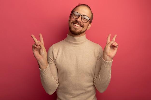 Glücklicher junger hübscher mann im beigen rollkragenpullover und in den gläsern, die vorne lächelnd fröhlich v-zeichen zeigend mit beiden händen betrachten, die über rosa wand stehen