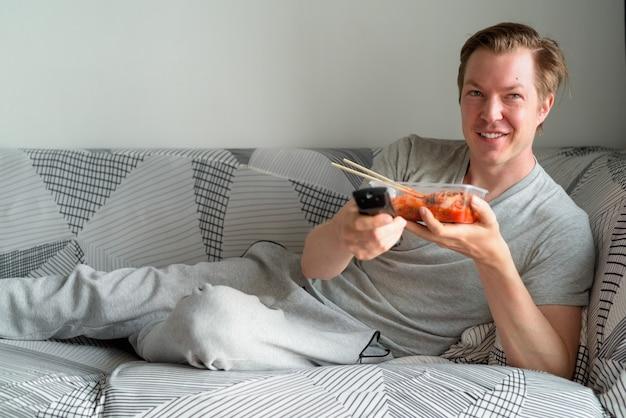 Glücklicher junger hübscher mann mit kimchi, der fernsieht und zu hause auf dem sofa liegt