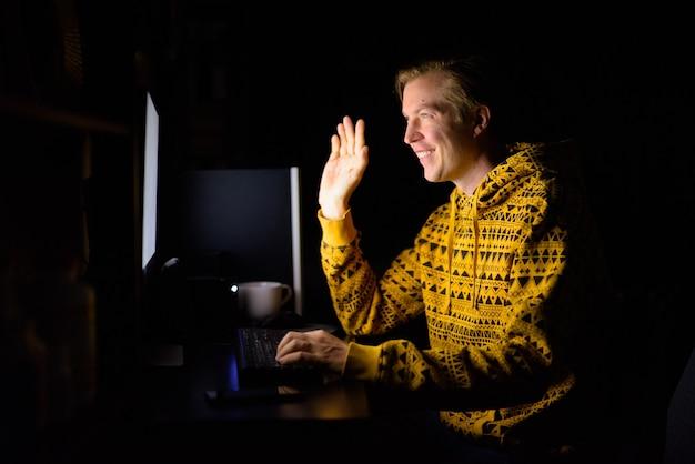Glücklicher junger hübscher mann videoanruf, während überstunden zu hause im dunkeln arbeiten