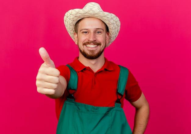 Glücklicher junger hübscher slawischer gärtner in der uniform und im hut, der daumen oben zeigt