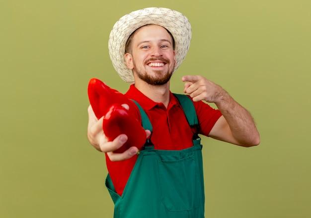 Glücklicher junger hübscher slawischer gärtner in der uniform und im hut, die streckende paprikaschoten suchen und zeigen, die auf olivgrüner wand mit kopienraum isoliert werden
