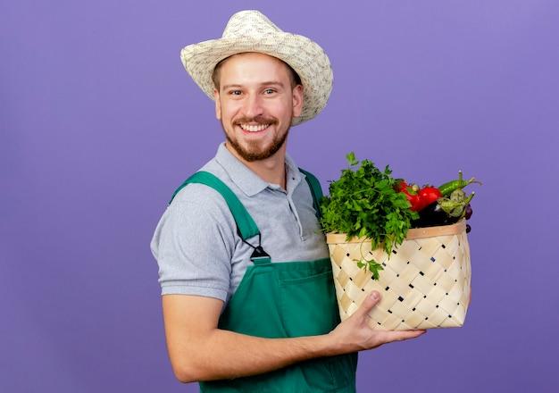 Glücklicher junger hübscher slawischer gärtner in uniform und hut, der korb des gemüses lokalisiert auf lila wand mit kopienraum hält