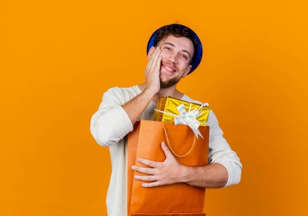 Glücklicher junger hübscher slawischer party-typ, der partyhut trägt, der geschenkboxen in der papiertüte hält, die hand auf gesicht lokalisiert auf orange hintergrund mit kopienraum hält