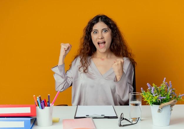 Glücklicher junger hübscher weiblicher büroangestellter, der am schreibtisch mit bürowerkzeugen sitzt, die ja geste lokalisiert auf orange wand zeigen