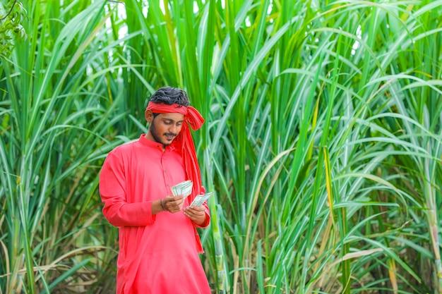 Glücklicher junger indischer bauer, der geld am zuckerrohrfeld zählt und zeigt