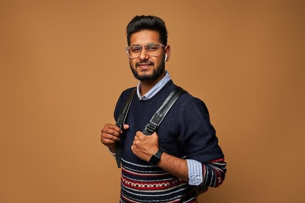 Glücklicher junger indischer student mit rucksack und brille in lässiger, stilvoller nähe an der wand.