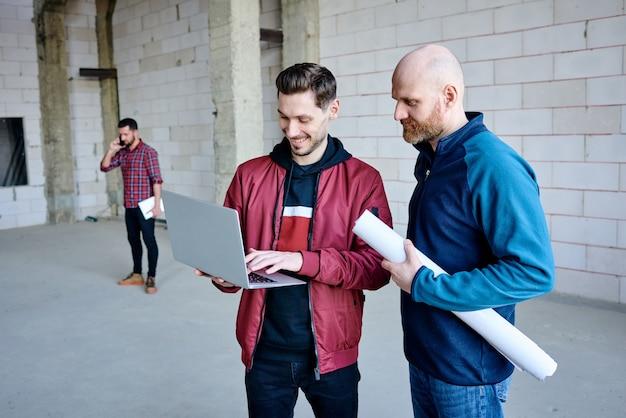 Glücklicher junger ingenieur, der laptop-tasten drückt, während er dem kollegen mit gerollter blaupause beim start-up-meeting ein neues projekt vorstellt