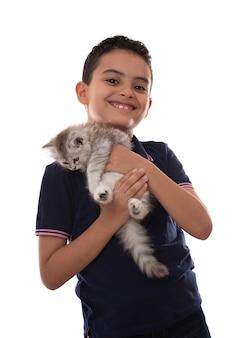 Glücklicher junger junge, der mit seinem pelzkätzchen lächelt