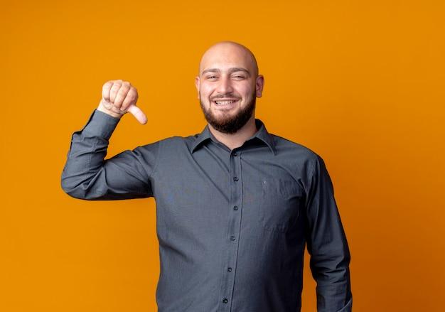 Glücklicher junger kahlköpfiger callcenter-mann, der auf sich selbst zeigt, isoliert auf orange