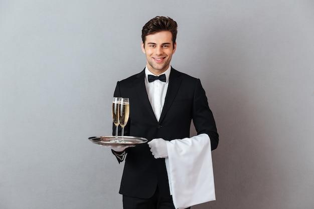 Glücklicher junger kellner, der glas champagner und tuch hält.