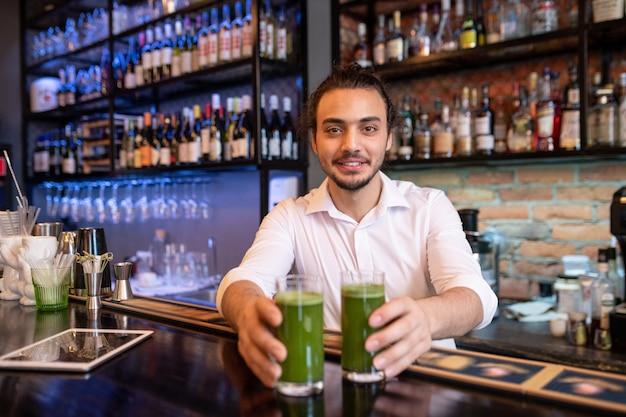 Glücklicher junger kellner oder barmann im weißen hemd, das sie zwei gläser frischen gemüsesmoothie mit flaschen alkohol auf hintergrund übergibt