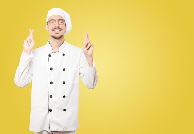 Glücklicher junger koch, der eine gekreuzte fingergeste tut