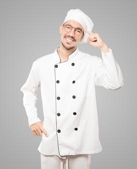 Glücklicher junger koch, der eine geste der konzentration tut