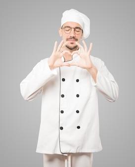 Glücklicher junger koch, der eine geste der liebe mit seinen händen tut