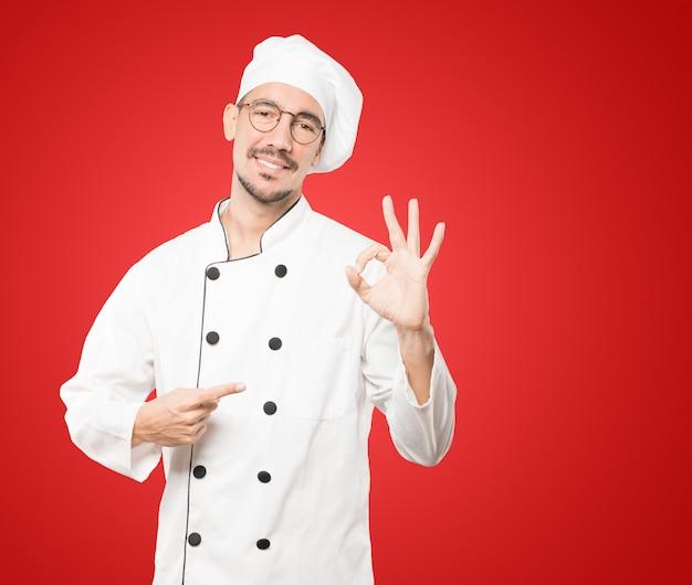 Glücklicher junger koch, der eine richtige geste tut