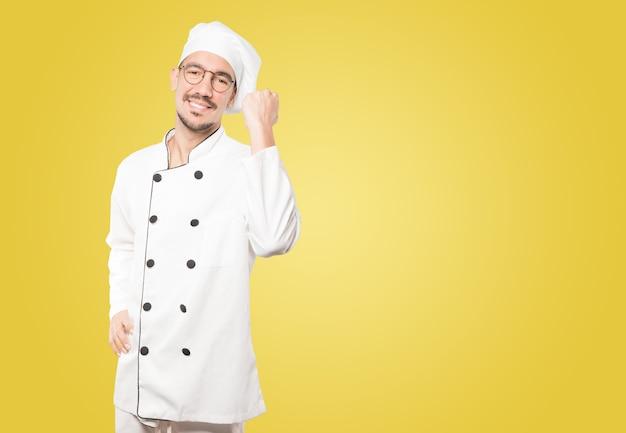 Glücklicher junger koch, der eine wettbewerbsfähige geste tut