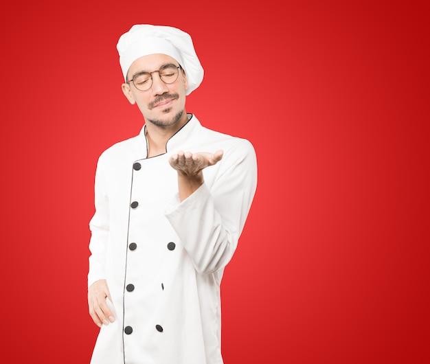 Glücklicher junger koch, der etwas mit seiner hand hält
