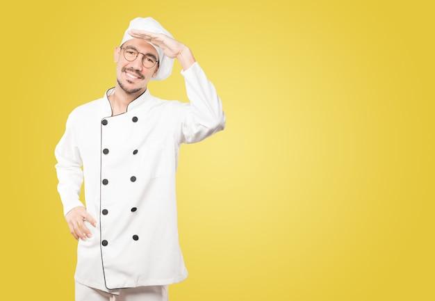 Glücklicher junger koch mit einer geste des wegschauens