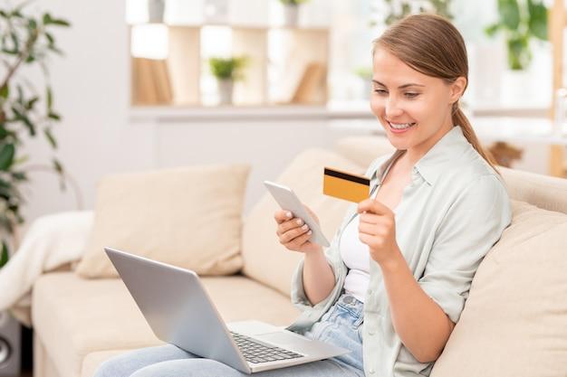 Glücklicher junger kunde in der freizeitkleidung, die auf couch sitzt, während bestellung im online-shop gemacht wird