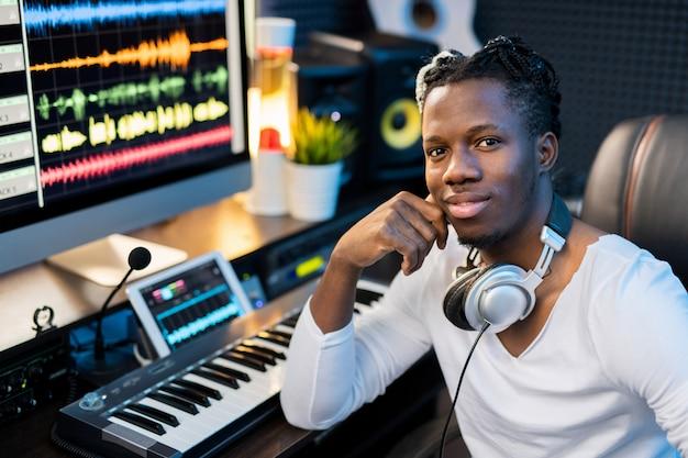 Glücklicher junger lächelnder mischlingsmann mit kopfhörern am hals, der am arbeitsplatz mit klaviertastatur und computermonitor sitzt