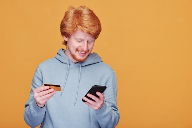 Glücklicher junger lässiger mann mit smartphone, der durch waren im online-shop rollt und mit kreditkarte bezahlt, während bestellung macht
