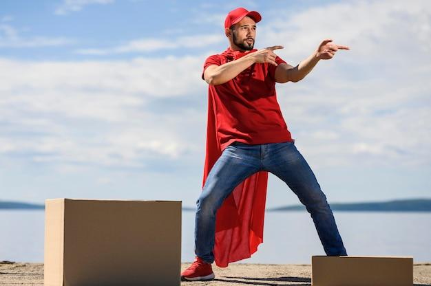 Glücklicher junger lieferbote, der superheldenumhang trägt