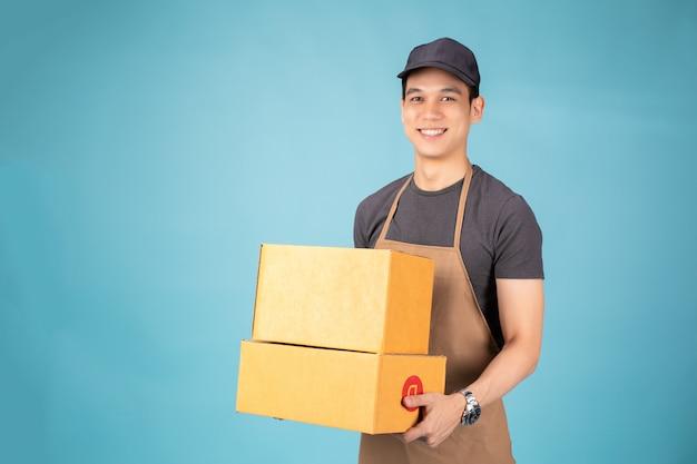 Glücklicher junger lieferbote in der schwarzen kappe, die mit paketbriefkasten steht