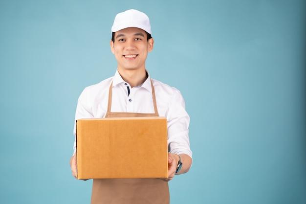 Glücklicher junger lieferbote in der weißen kappe, die mit paketbriefkasten steht