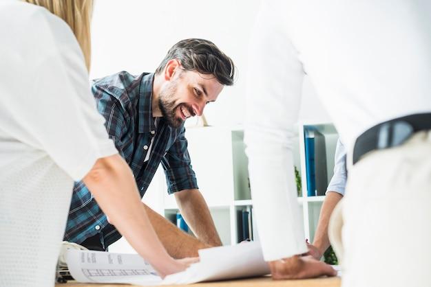 Glücklicher junger männlicher architekt, der plan betrachtet